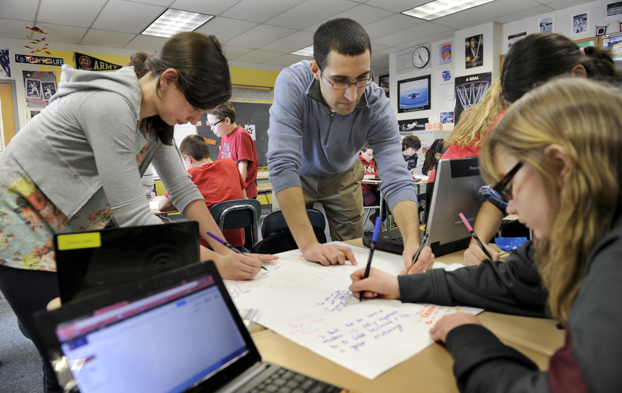 Teacher Joel Pardalis, center, works with students in his sixth-grade language arts class at New Fairfield Middle School in New Fairfield, Conn. Thursday, March 21, 2013.