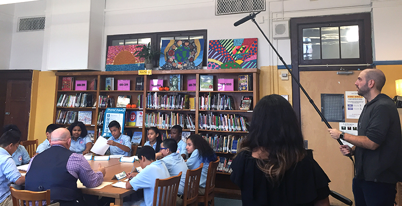 """Students at The Lexington Academy discuss """"The New Colossus"""" with Great Books instructor Fred Hang while being filmed for CBS News."""