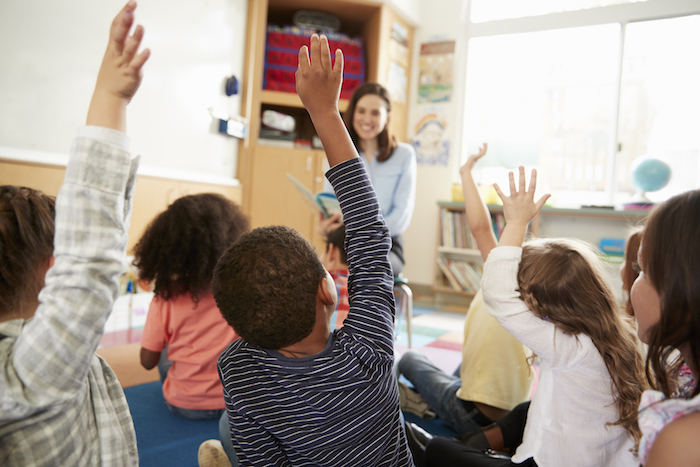 Inquiry-based learning activity student questions elementary school kids raising hands to teacher