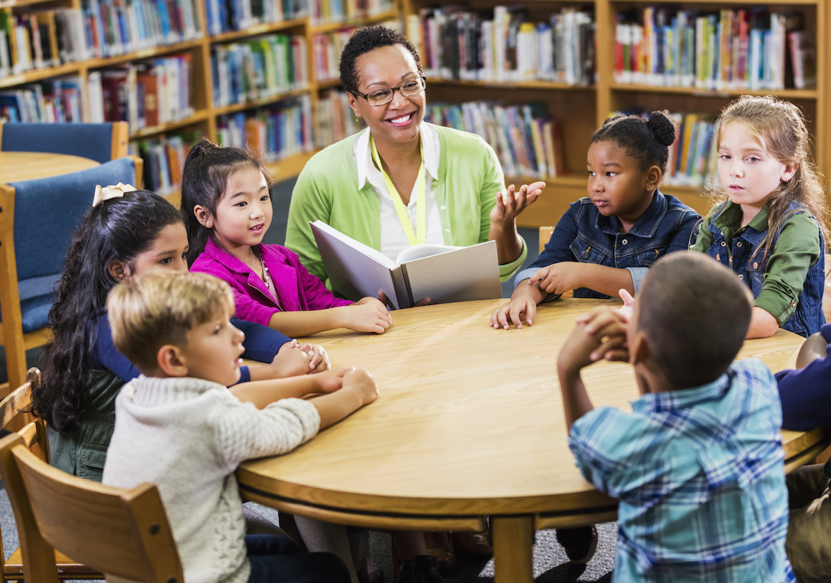 Teacher using reading comprehension strategies for children in library